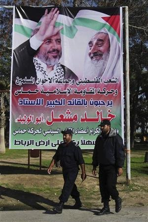Members of Hamas security forces walk past a poster depicting Hamas chief Khaled Meshaal (L) and late Hamas spiritual leader Ahmed Yassin (R), at Rafah crossing in the southern Gaza Strip December 6, 2012. REUTERS/Ibraheem Abu Mustafa