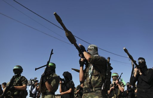 """Palestinian members of the al-Qassam brigades, the armed wing of the Hamas movement, stand guard as they wait for the arrival of Hamas chief Khaled Meshaal in Rafah in the southern Gaza Strip December 7, 2012. Meshaal, Hamas's exiled leader, will step onto Palestinian land for the first time in 45 years on Friday for a """"victory rally"""" in the Gaza Strip, displaying his newfound confidence after last month's conflict with Israel. Meshaal, the Islamist group's leader, who has not visited the Palestinian Territories since leaving the West Bank at age 11, emerged emboldened from the eight-day conflict which ended in a truce he negotiated under Egypt's auspices. He has since spoken of reaching out to other Palestinian factions. REUTERS/Mohammed Salem"""
