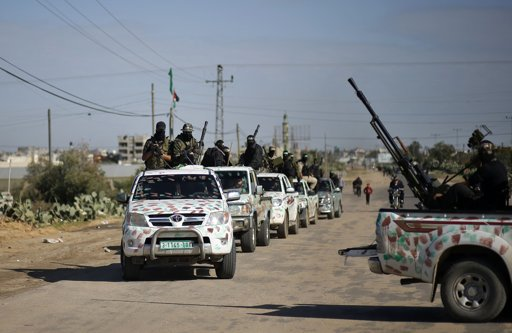 "Palestinian members of the al-Qassam brigades, the armed wing of the Hamas movement, ride in pickup trucks as they await the arrival of Hamas chief Khaled Meshaal in Rafah in the southern Gaza Strip December 7, 2012. Hamas's exiled leader Meshaal will step onto Palestinian land for the first time in 45 years on Friday for a ""victory rally"" in the Gaza Strip, displaying his newfound confidence after last month's conflict with Israel. Meshaal, the Islamist group's leader, who has not visited the Palestinian Territories since leaving the West Bank at age 11, emerged emboldened from the eight-day conflict which ended in a truce he negotiated under Egypt's auspices. He has since spoken of reaching out to other Palestinian factions. EUTERS/Mohammed Salem"