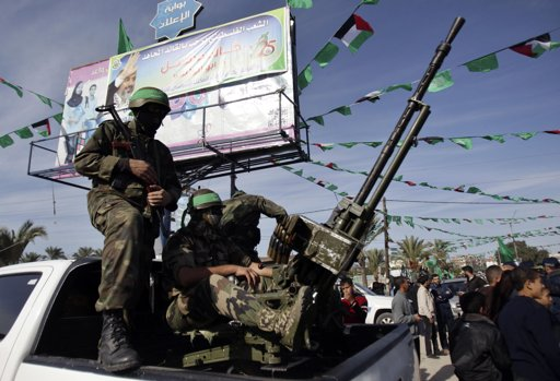 Palestinian members of the al-Qassam brigades, the armed wing of the Hamas movement, ride in pickup trucks as they await the arrival of Hamas chief Khaled Meshaal in Khan Younis in the southern Gaza - Photo by Ibraheem Abu Mustafa