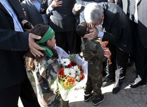 Hamas chief Khaled Meshaal kisses a Palestinian boy upon his arrival at the Rafah crossing in the southern Gaza Strip December 7, 2012. Meshaal arrived in the Gaza Strip on Friday,  Photo by Ahmad Jadallah