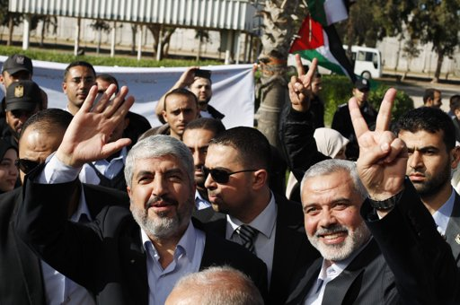 Hamas chief Khaled Meshaal (L) waves as he stands next to senior Hamas leader Ismail Haniyeh upon Meshaal's arrival at Rafah crossing in the southern Gaza Strip December 7, 2012.  Photo By SUHAIB SALEM/REUTERS