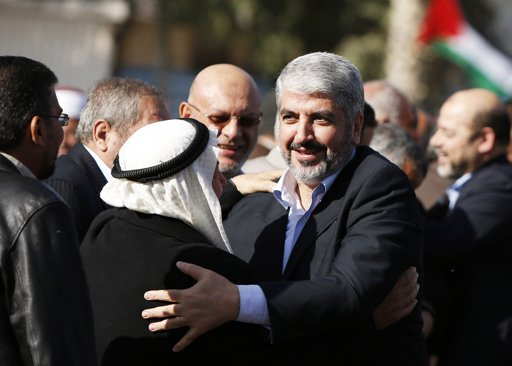 A Palestinian man hugs Hamas chief Khaled Meshaal (R) upon his arrival at Rafah crossing in the southern Gaza Strip December 7, 2012. Photo By SUHAIB SALEM/REUTERS
