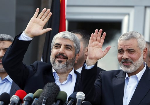 Hamas chief Khaled Meshaal (R) and senior Hamas leader Ismail Haniyeh wave during a news conference upon Meshaal's arrival at Rafah crossing in the southern Gaza Strip December 7, 2012. Meshaal arrived in the Gaza Strip on Friday, ending 45 years of exile from Palestinian land with a visit that underscored the Islamist group's growing confidence following a recent conflict with Israel. REUTERS/Suhaib Salem