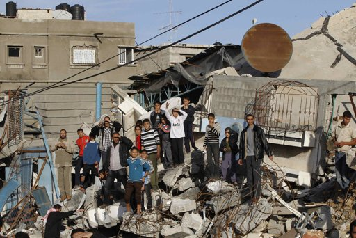 Palestinians stand on the rubble of a house, which witnesses said was destroyed in an Israeli air strike, as they watch the convoy of Hamas leader Khaled Meshaal in Gaza City December 7, 2012 - Photo by Ahmed JadAllah