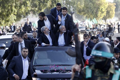 Hamas chief Khaled Meshaal (L) rides in a car with senior Hamas leader Ismail Haniyeh as they wave to the crowd upon his arrival in the southern Gaza Strip December 7, 2012. - Photo by Ahmed Jadallah
