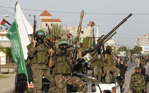 Palestinian members of the al-Qassam brigades, the armed wing of the Hamas movement, ride in pickup trucks as they follow the convoy of Hamas leader Khaled Meshaal in Gaza City December 7, 2012 - Photo by Ahmed Jadallah