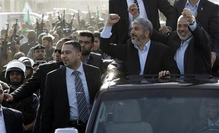 Hamas chief Khaled Meshaal (2nd R), riding in a car with senior Hamas leader Ismail Haniyeh (R), gestures to the crowd upon his arrival in Gaza City December 7, 2012. - Photo by Mohammed Salem / Reuters