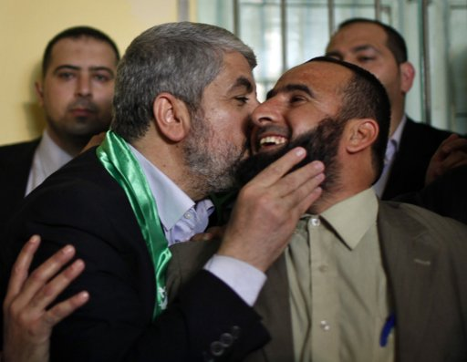 Hamas leader Khaled Meshaal (L) kisses Abed Al-Ghani, the son of late Hamas founder Sheikh Ahmed Yassin, in Gaza City December 7, 2012