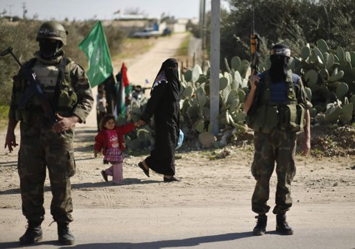 A woman and a child walk past Palestinian members of the al-Qassam brigades, the armed wing of the Hamas movement, standing guard while waiting for the convoy of Hamas leader Khaled Meshaal . Photo by Mohammed Salem
