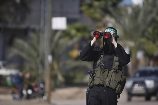 A Palestinian member of the al-Qassam brigades, the armed wing of the Hamas movement, looks through a pair of binoculars as he waits for the convoy of Hamas leader Khaled Meshaal in the southern Gaza - Photo by Ibraheem Abu Mustafa