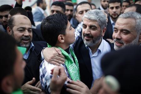 Hamas chief Khaled Meshaal (2nd R) hugs the son of late Hamas military commander Ahmed al-Jaabari, who was killed in an Israeli air strike, in Gaza City December 7, 2012. REUTERS/Ahmed Jadallah