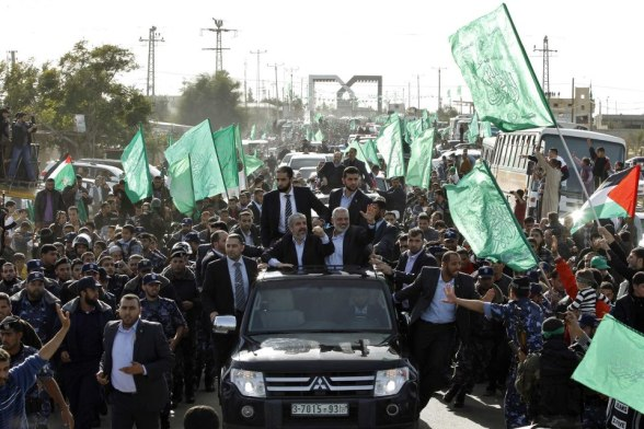 Hamas chief Khaled Meshaal (L), riding in a car with senior Hamas leader Ismail Haniyeh (R), waves to the crowd upon his arrival in the southern Gaza Strip December 7, 2012. Meshaal ended decades of exile from Palestinian land on Friday with a triumphal first ever visit to the Gaza Strip that underscored the Islamist group's growing confidence following its latest conflict with Israel. REUTERS/Ahmed Jadallah