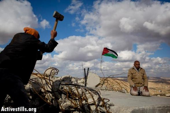 Al-Mufaqara, South Hebron, West Bank, 22.12.2012  A Palestinian man brakes concrete slabs, that used to be a wall of a mosque, demolished for the second times by Israeli authorities a few days ago, while an elder Palestinian prays in the West Bank village of Al-Mufaqara, south of Hebron, December 21, 2012. Palestinian, Israeli and international activists joined the residents of the village for a solidarity action, after the village's mosque was demolished 2 weeks ago by Israeli authorities.  Photo by: Oren Ziv/ Activestills.org