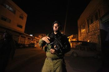 An Israeli soldier holds his gun after clashes with Palestinians in the West bank town of Hebron on December 12, 2012. Photo by Hazem Bader