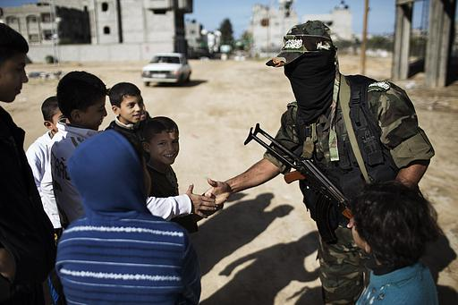 A Palestinian boy holding a poster depicting Hamas chief Khaled Meshaal stands next to a member of the al-Qassam brigades, the armed wing of the Hamas movement, as they wait for Meshaal's convoy  Photo by Ahmad Jadallah
