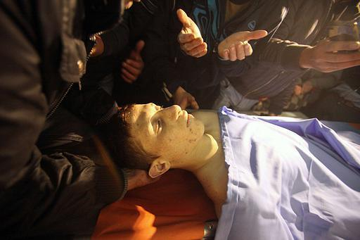Palestinians carry the body of 16-year-old Palestinian Mohammed Ziad Sulaima at a hospital in the old city of the West bank town of Hebron on December 12, 2012. Israeli border guards shot dead a Palestinian teenager armed with a fake pistol, a police spokeswoman said, adding that clashes broke out after the shooting. AFP PHOTO / HAZEM BADER