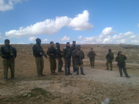 All this Israeli army with their american weapons standing in front of unarmed people building