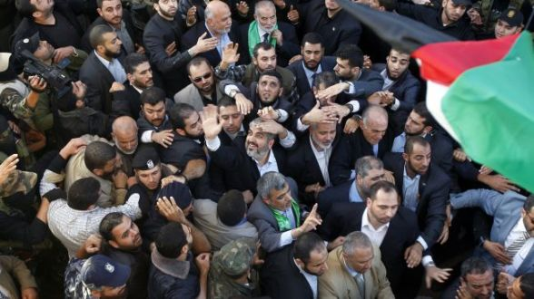 Hamas Political Bureau Chief Khaled Meshaal (center waving) greet Palestinians upon arrival in Gaza City on December 7, 2012.