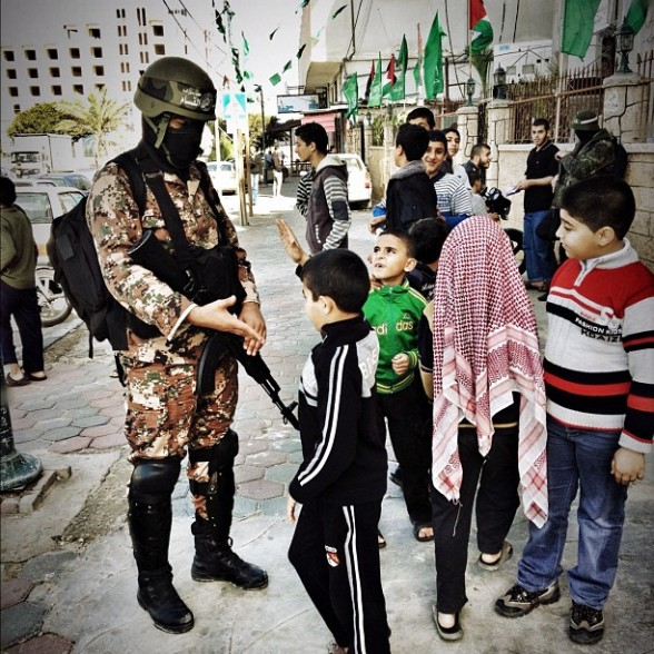 Photo by boutainaab -  Qassam Brigades fighter greeting children in Gaza today