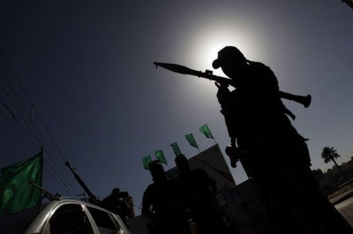 """A Palestinian militant of the Ezzedine al-Qassam brigade, the armed wing Hamas, stands guard as they prepare for the arrival of Khaled Meshaal who is due in the Gaza Strip to celebrate its 25th anniversary of the Islamist movement. Meshaal has crossed into the Gaza Strip on his first-ever visit, kissing the ground and hoping he would one day die a """"martyr"""" in the Palestinian territory"""