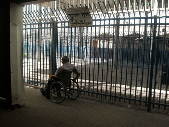 "Man in wheelchair going through the ""humanitarian"" lane in Qalandiya Checkpoint, June 2011. Photo by Irus Braverman"