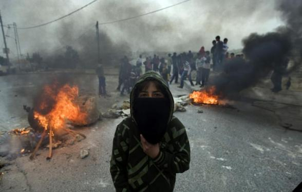 A masked Palestinian youth covers his face during clashes with Israeli security forces in the east Jerusalem neighborhood of Issawiya on 14 February 2012 (Photo: AFP - Ahmad Gharabli)