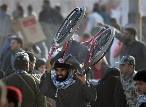 A Palestinian carries a wheelchair bought in Egypt across the border back to Gaza after militants exploded the border wall between Gaza Strip and Egypt, in Rafah, on Jan. 24, 2008