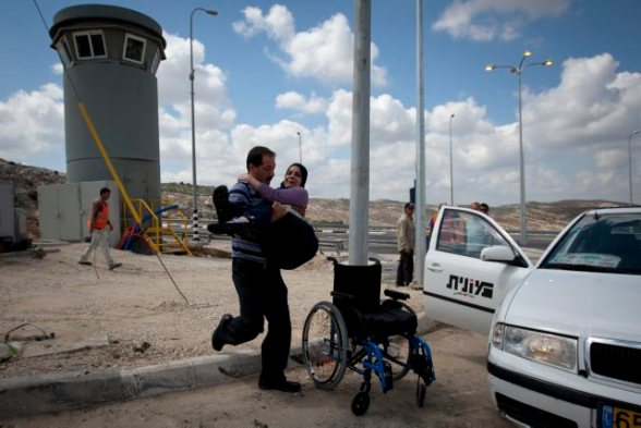 An Arab-Israeli taxi driver carries a disabled Palestinian woman arriving from Jerusalem, from his taxi to her sister's vehicle, that awaits next to the new checkpoint on route 443 near the village of Beit Our, since Palestinian vehicles are denied access to the 443 route, May 24, 2010. The Israeli Supreme court issued an order, allowing Palestinian drivers to use route 443, Starting Friday. The road cuts through the occupied West Bank and links Jerusalem and Israel's coastal plain. - Photo by Photo-Op