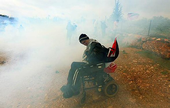 Wheelchair bound protester in West Bank surrounded by clouds of tear gas