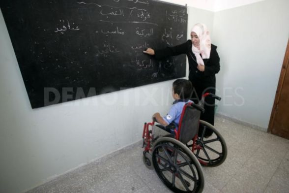 School for the physically disabled under the joint cooperation of the united Palestinian appeal and the welfare association, Gaza, Palestinian Territory, 27/10/2009. Physically disabled Palestinian students attend lessons in a class at The School Rehabilitation of physically disabled, at Rafah town in the southern Gaza Strip on October 27, 2009.School of the physically disabled this project has been executed under the joint cooperation of the united palestinian appeal and the welfare association established in 2004 with the sponsorship of by the Agency the U.S for international development,teach some 100 students disableds in the school, faces the threat of closure because of the longstanding Israeli blockade on the Gaza Strip.. Photo by Abed Rahim Khatib