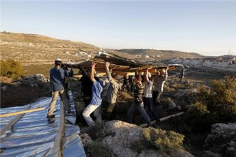 Jewish settlers carry wooden planks as they build a structure at an  unauthorized outpost near the settlement of Kiryat Arba outside the  West Bank city of Hebron in 2012. (Reuters/Baz Ratner, File)