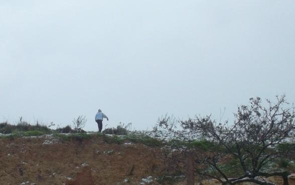Settler breaking olive trees in Qusra