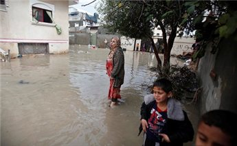 A Palestinian woman reacts as floodwaters flow into her house after<br /><p class=