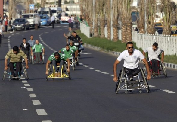 Wheelchair-bound Palestinians take part in a one-kilometer race for people with physical disabilities in Gaza City November 8, 2012. The race was organised by a local club in coordination with the Palestinian Paralympic Committee. REUTERS/Ahmed Zakot