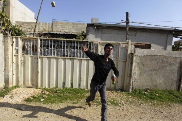 A Palestinian protester throws a stone as he holds a Molotov cocktail during clashes with Israeli security officers in the West Bank village of Tamoun, near the West Bank city of Jenin January 1, 2013. Clashes broke out after an Israeli military operation in the village on Tuesday. REUTERS/Ammar Awad