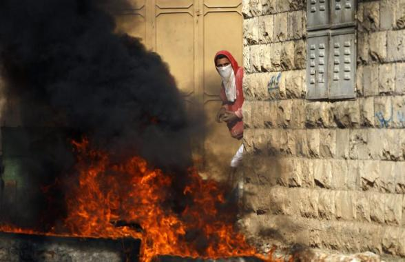 A stone-throwing Palestinian protester stands near burning tyres during clashes with Israeli security officers in the West Bank village of Tamoun, near the West Bank city of Jenin January 1, 2013. Clashes broke out after an Israeli military operation in the village on Tuesday. REUTERS/Ammar Awad