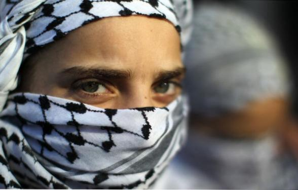 A masked Palestinian girl attends a protest calling for the release of Palestinian prisoners from Israeli jails outside the International Red Cross offices in Gaza on 21 January 2013. (Photo: AFP - Mahmud Hams)