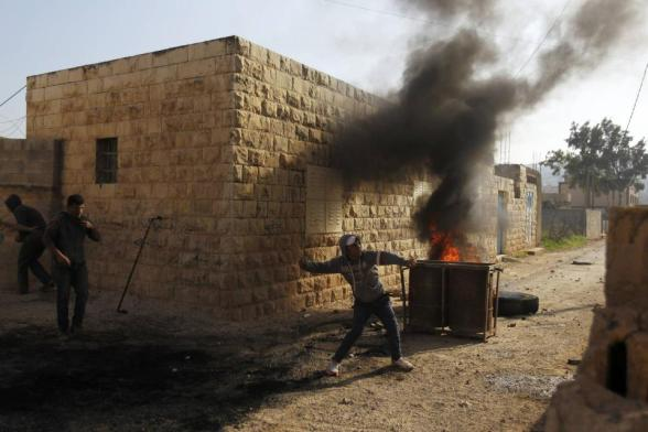 A Palestinian protester throws a stone near burning tyres during clashes with Israeli security officers in the West Bank village of Tamoun, near the West Bank city of Jenin January 1, 2013. Clashes broke out after an Israeli military operation in the village on Tuesday. REUTERS/Ammar Awad