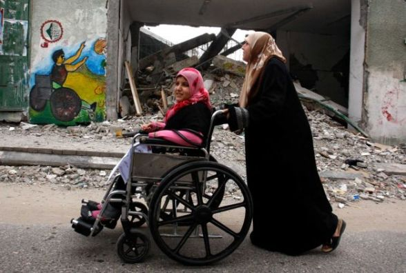 "A Palestinian woman pushes a girl in a wheelchair past a destroyed stadium during a march to mark the UN International Day of People with Disability in Gaza City, Tuesday, Dec. 4, 2012. Each year the day focuses on a different issue and the theme this year is ""Removing barriers to create an inclusive and accessible society for all."" (AP Photo/Hatem Moussa)"