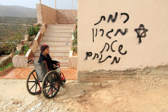 A Palestinian boy in a wheelchair looks at a hate slogans in hebrew painted by extremist settlers on the facade of his home in the village of Majdal, near the West Bank City of Nablus, 20 December 2012. According to Palestinian security officials two cars were set on fire in a raid by Jewish settlers in the village of Majdal. Credit: EPA