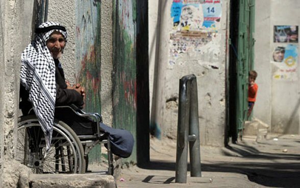Palestinian man sits in his wheelchair in front of his house in the Al Azza refugee camp in the West Bank town of Bethlehem March 30, 2006. (MaanImages/Magnus Johansson)