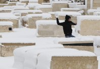 A Palestinian throws a snowball in the snow-covered Jewish cemetery on the Mount of Olives in Jerusalem January 10, 2013. The worst snowstorm in 20 years shut government offices, public transport and schools in Jerusalem and along the northern Israeli region bordering on Lebanon on Thursday. REUTERS/Baz Ratner