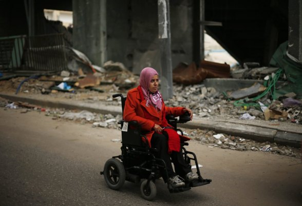 Dec 4 2012 disabled Palestinian woman rides wheelchair past a soccer stadium destroyed in  air strike during an eight-day war on Gaza - Photo by  Suhaib Salem