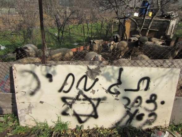 Israeli settlers burn two vehicles and spray paint racist slogans on a Palestinian home in Beit Ummar