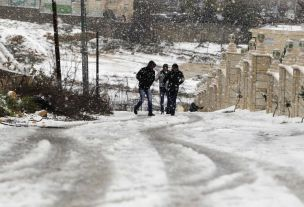 Palestinian walk along a snow covered road in the West Bank village of Halhul near Hebron January 9, 2013. At least 17 people have died due to a winter storm in Lebanon, Jordan, Turkey, Israel and the Palestinian territories. Meteorological agencies in Israel and Lebanon both called it the worst storm in 20 years. REUTERS/Ammar Awad