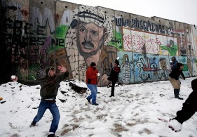 Palestinians play in the snow next to a section of Israel's barrier