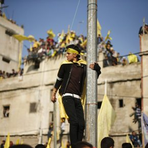 A Palestinian man climbs an electric pole as others watch a rally marking the 48th anniversary of the founding of the Fatah movement, in Gaza City January 4, 2013. Hundreds of thousands of Palestinians joined a rare rally staged by President Mahmoud Abbas's Fatah group in Gaza on Friday, as tensions ease with rival Hamas Islamists ruling the enclave since 2007. REUTERS/Suhaib Salem