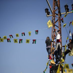 Palestinians climb an electric pole during a rally marking the 48th anniversary of the founding of the Fatah movement, in Gaza City January 4, 2013. Hundreds of thousands of Palestinians joined a rare rally staged by President Mahmoud Abbas's Fatah group in Gaza on Friday, as tensions ease with rival Hamas Islamists ruling the enclave since 2007. REUTERS/Mohammed Salem