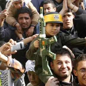 A Palestinian boy holds a toy gun during a rally in the West Bank city of Nablus marking the 48th anniversary of the founding of the Fatah movement January 3, 2013. REUTERS/Abed Omar Qusini